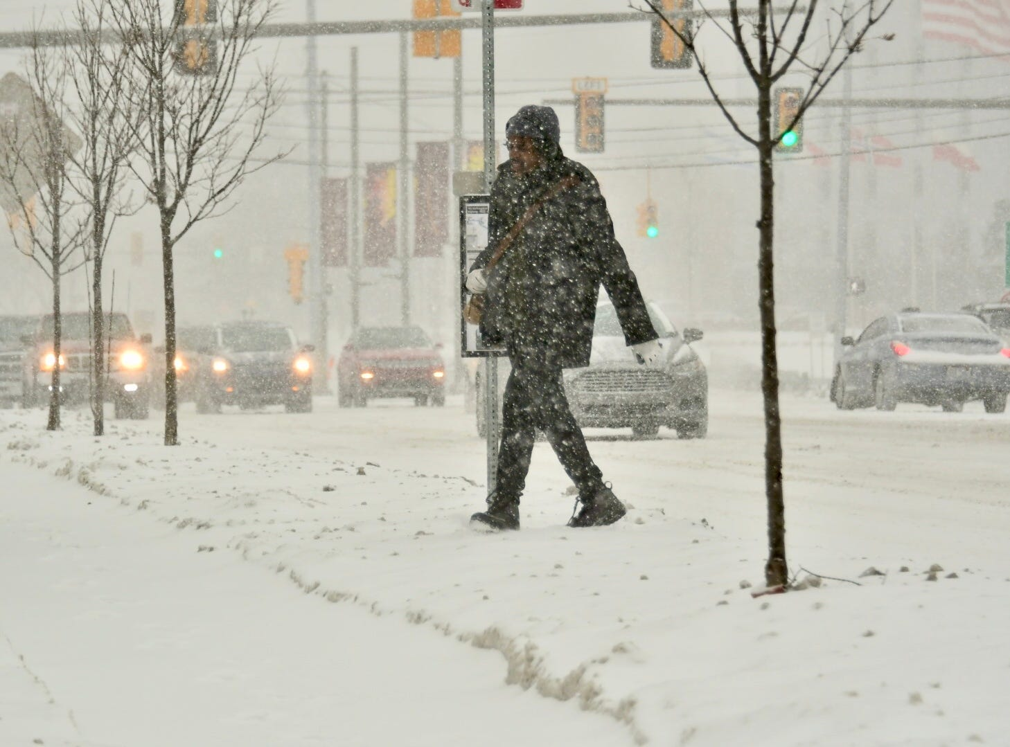 Pedestrians and vehicles make their way through the snow on Evergreen in Southfield, Monday afternoon,