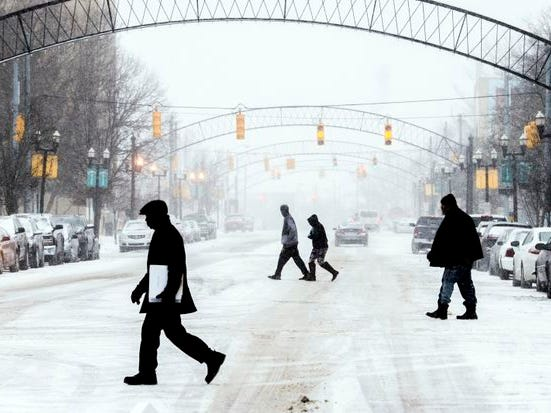Defense attorney Archie Hayman, a former Genesee County Circuit judge, walks in silhouette along with three other men crossing Saginaw Street in Flint during a winter storm on Monday in downtown Flint.