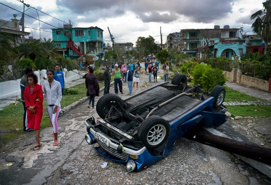 A car overturned by a tornado lays smashed on top of a street pole in Havana, Cuba, Monday, Jan. 28, 2019.