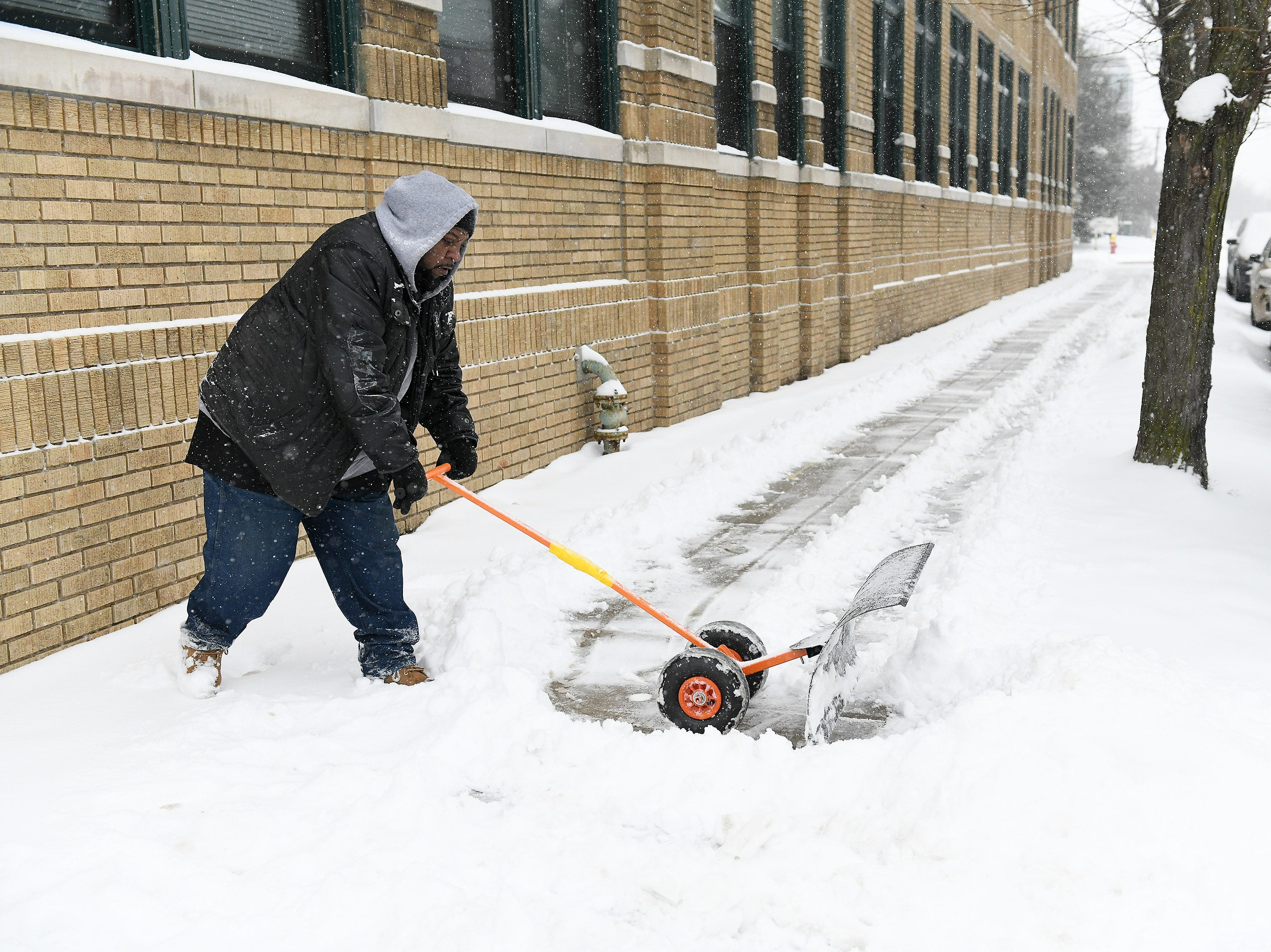 Walter Houze uses a rolling shovel to remove snow from the sidewalk outside the Kirby Lofts in Detroit on Jan. 28, 2019.