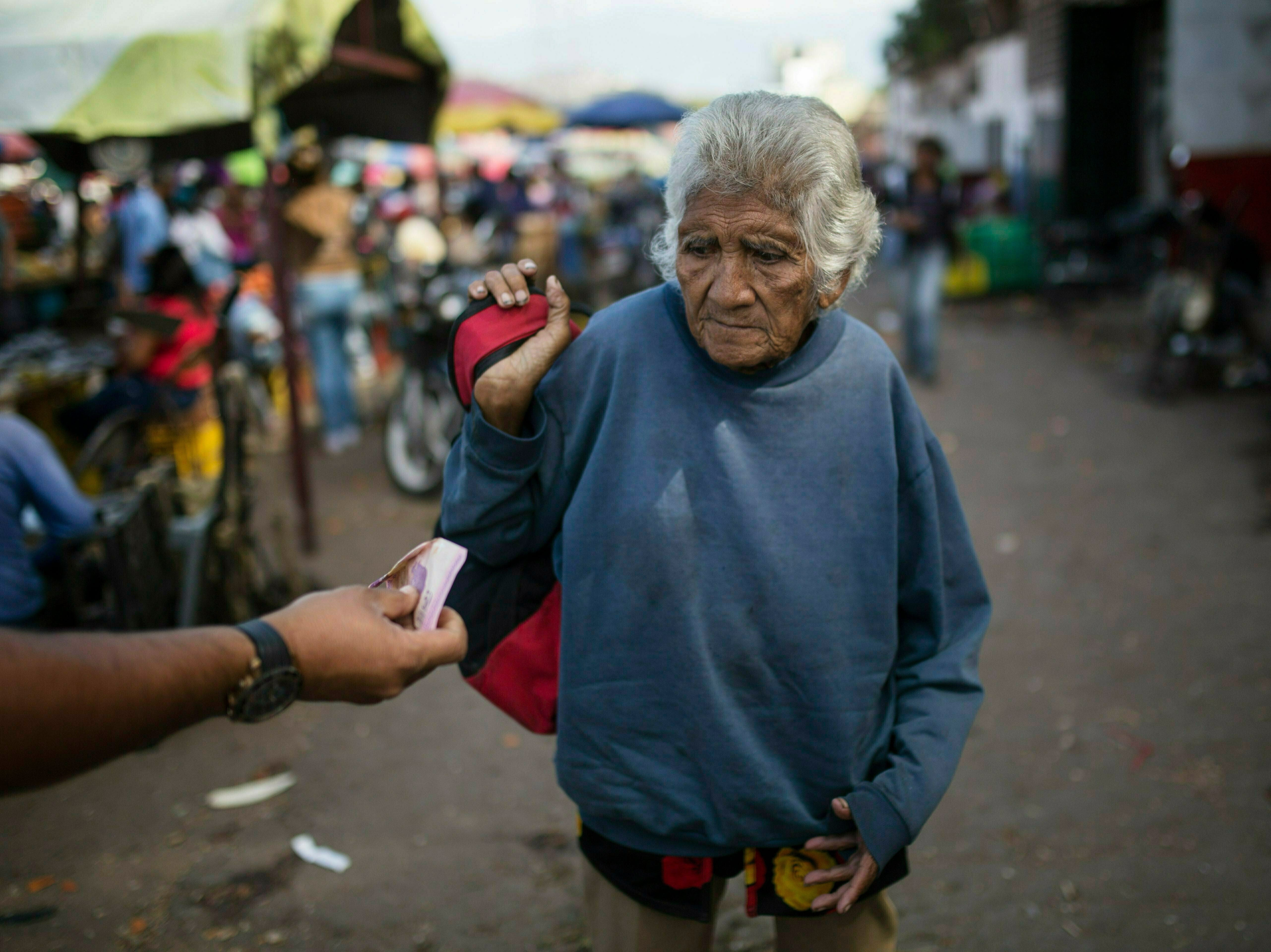 An elderly woman is offered cash as she begs at a wholesale food market in Caracas, Venezuela, Monday, Jan. 28, 2019. Economists agree that the longer the standoff between the U.S.-backed opposition leader Juan Guaido and President Nicolas Maduro drags on, the more regular Venezuelans are likely to suffer.