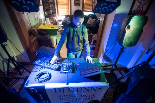 """In this Wednesday, Jan. 16, 2019 photo, flashing lights illuminate the living room of the Port Huron, Mich., home where Gunner Welch, 14, also known as """"DJ Gunns,"""" plays through a playlist of electronic dance music."""