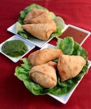 Chicken samosas with mint chutney, left, and tamarind chutney, right.