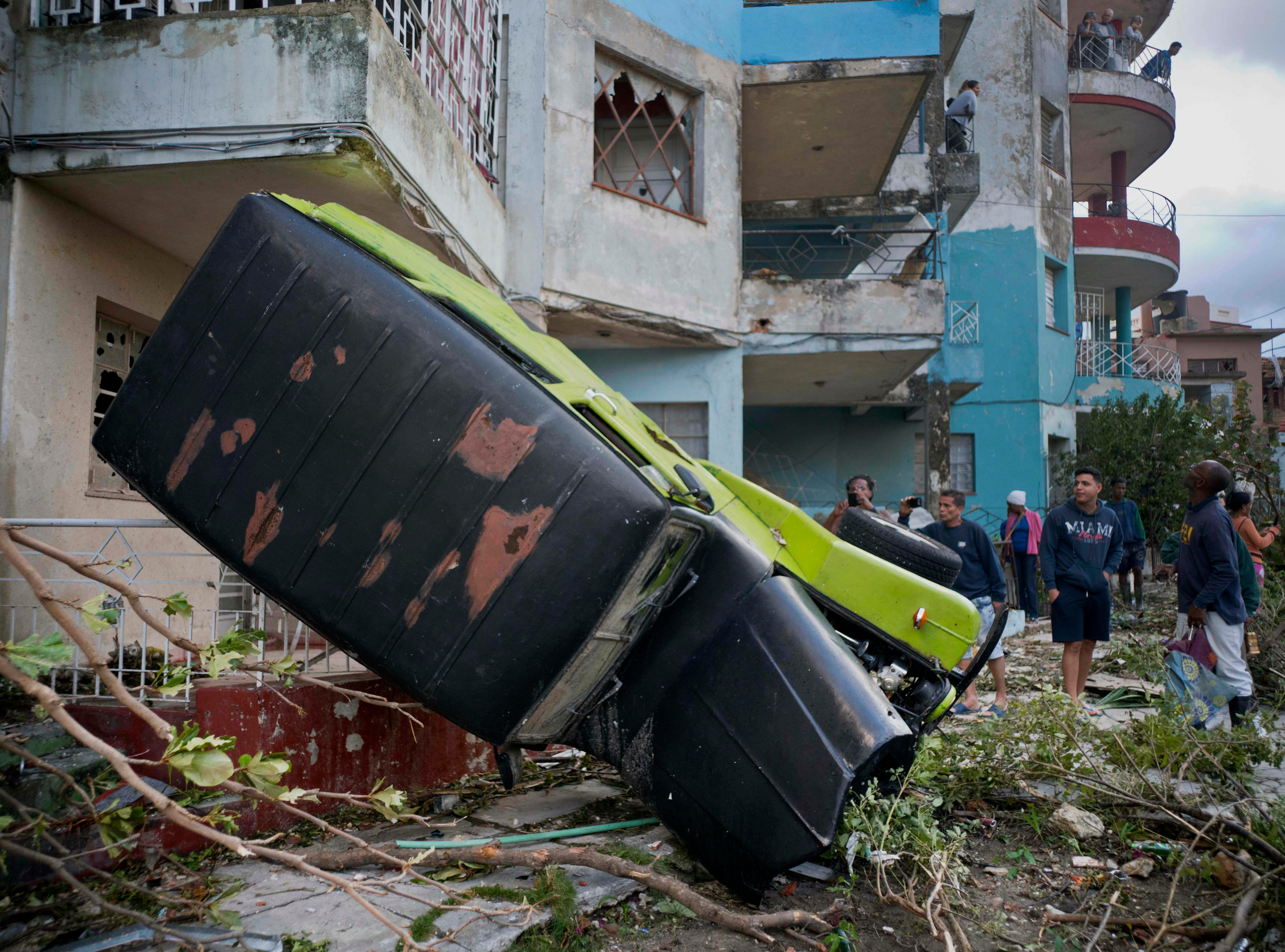 A truck is toppled against a home after a tornado in Havana, Cuba, Monday, Jan. 28, 2019.