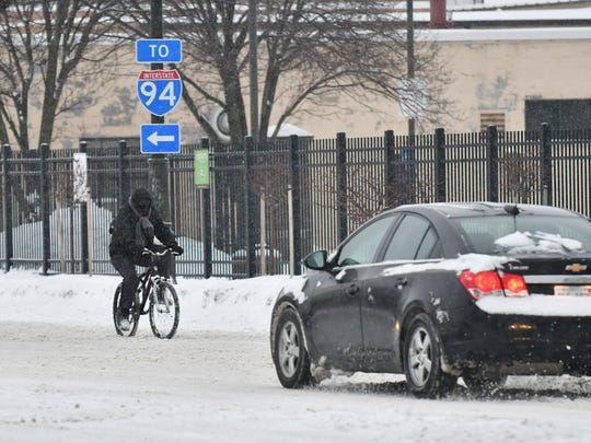 A man rides a bicycle in the snow up Woodward Avenue in Detroit on Jan. 28, 2019.  (Robin Buckson / The Detroit News)