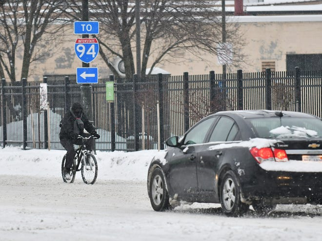 A man rides a bicycle in the snow up Woodward Avenue in Detroit on Jan. 28, 2019.  
