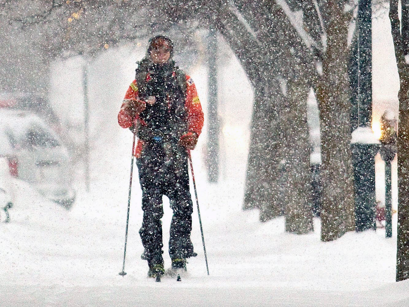 Mike Powers cross country skis to work in downtown Traverse City, Monday.