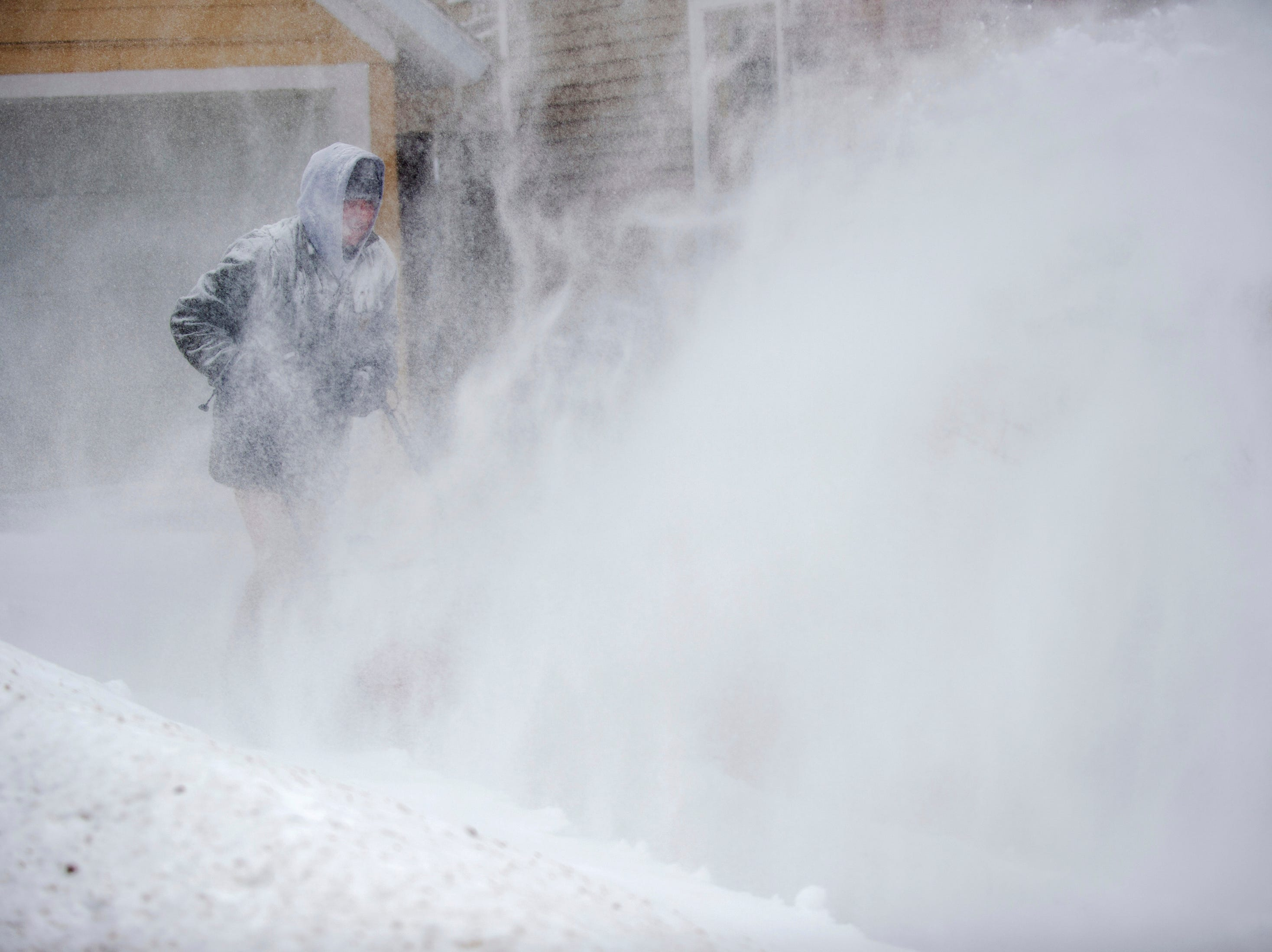 Erik Johnson clears snow from his neighbor's driveway in East Grand Rapids,  Monday.