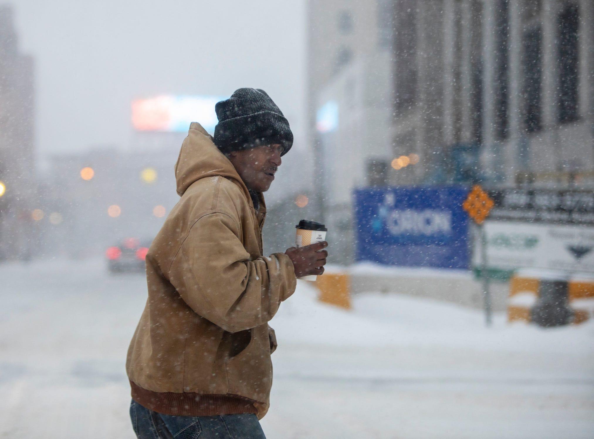 A man crosses Michigan Avenue through blowing snow Monday in downtown Kalamazoo.