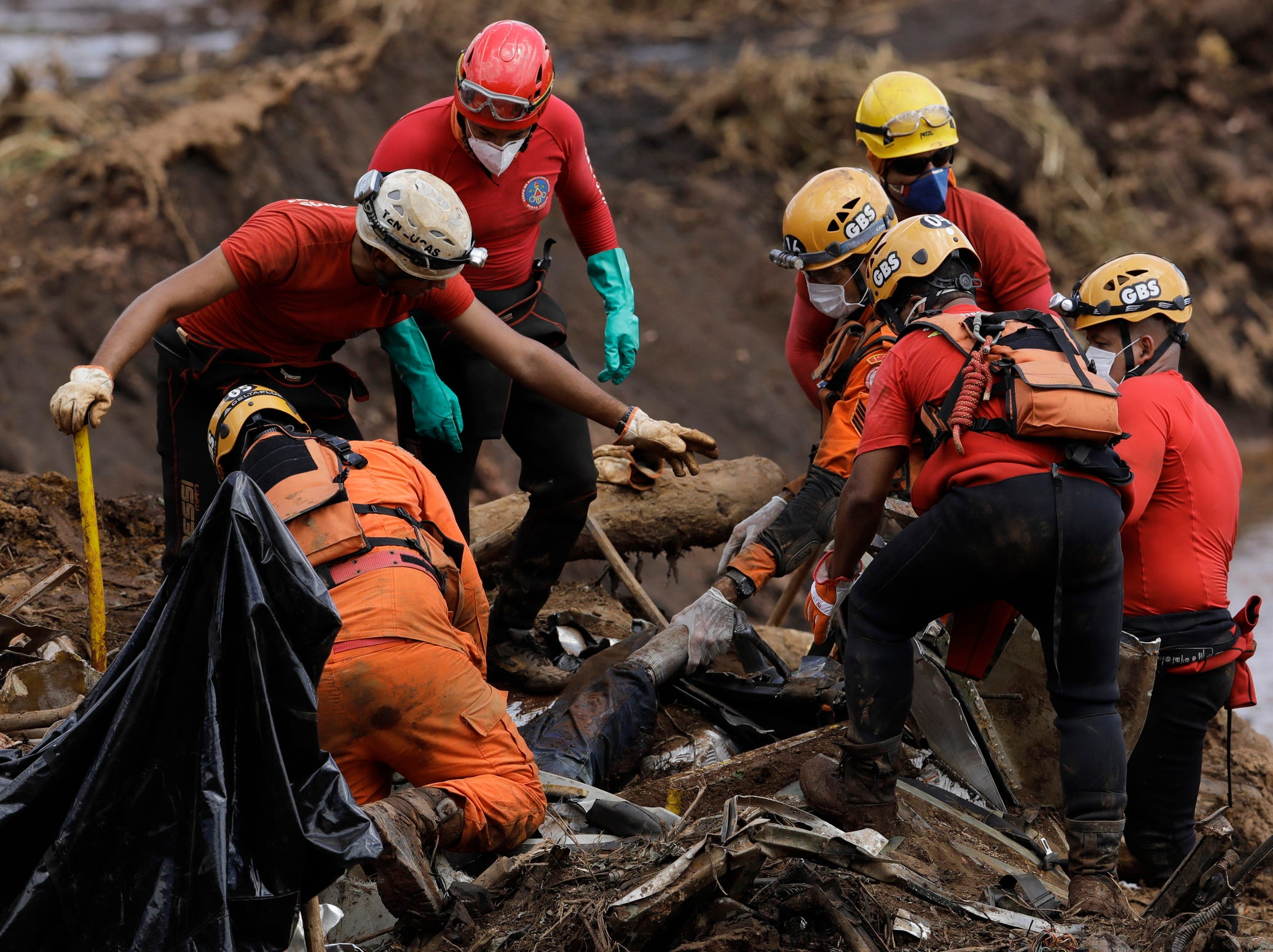 Firefighters pull a body from the mud days after a dam collapse in Brumadinho, Brazil, Monday, Jan. 28, 2019. The dam collapse buried mine buildings and surrounding neighborhoods with iron ore waste.