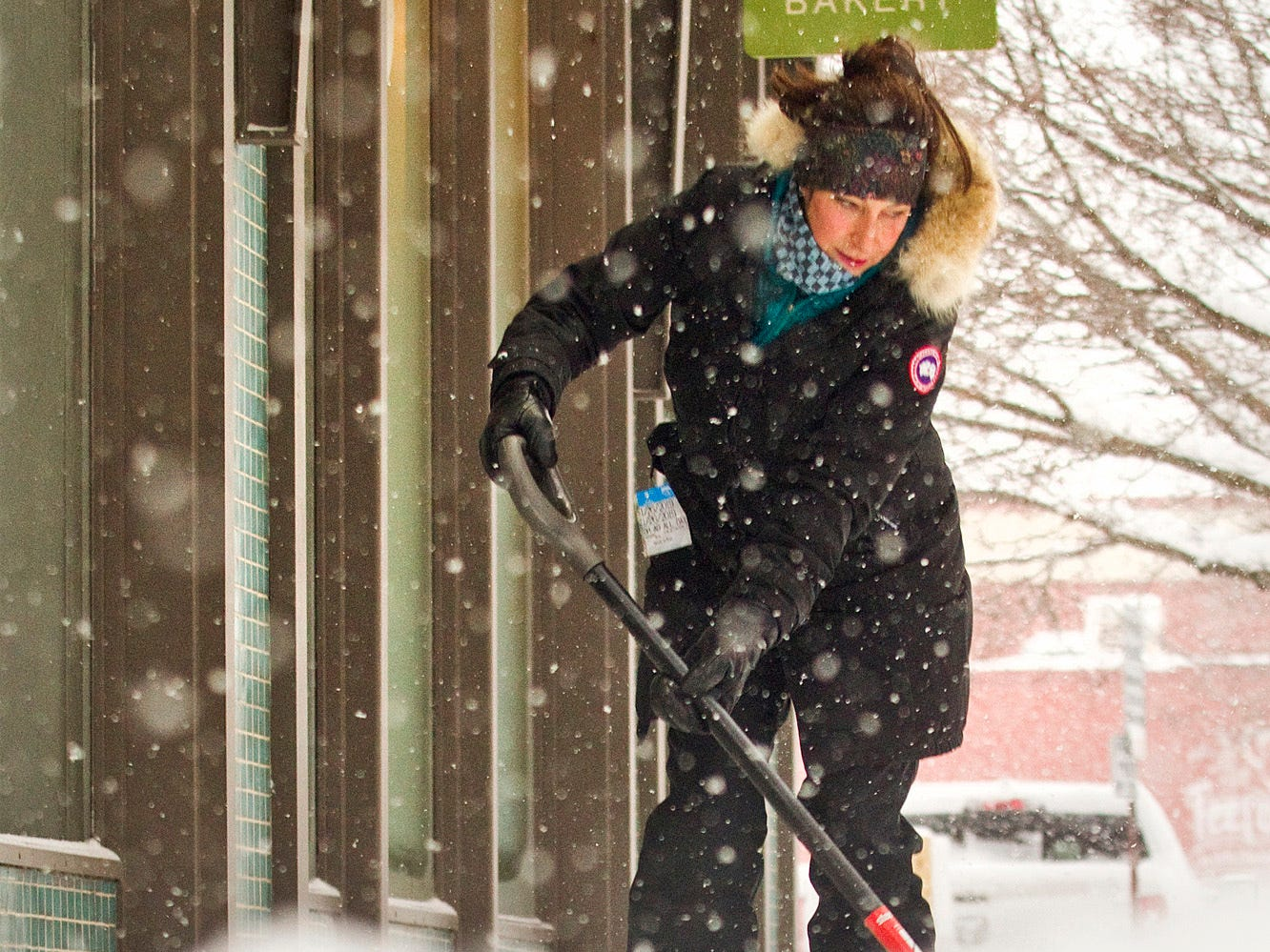 """Kara McConnell shovels snow outside of Good Harbor Coffee and Bakery on Monday morning in Traverse City. McConnell, a teacher at Eastern Elementary School, volunteered to shovel since she had free time on the snow day. """"Just getting a coffee and trying to be helpful,"""" she said."""