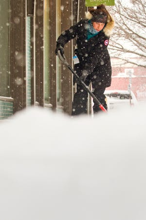 "Kara McConnell shovels snow outside of Good Harbor Coffee and Bakery on Monday morning in Traverse City. McConnell, a teacher at Eastern Elementary School, volunteered to shovel since she had free time on the snow day. ""Just getting a coffee and trying to be helpful,"" she said."