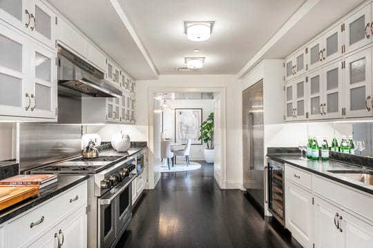 White cabinets with frost glass inserts provide storage and privacy. (Design Recipes)