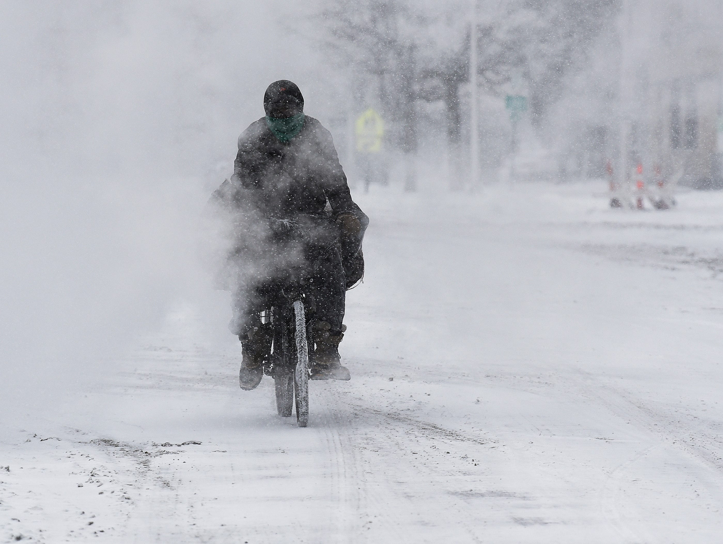 """Melvyn """"Mello"""" Burrell, 46, of Detroit, rides his bike through the steam on Ledyard and Second streets in Detroit on his way to the store, Monday, January 28, 2019."""
