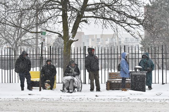 As snow falls, people wait at a bus stop on Mack Avenue in Detroit Monday afternoon.