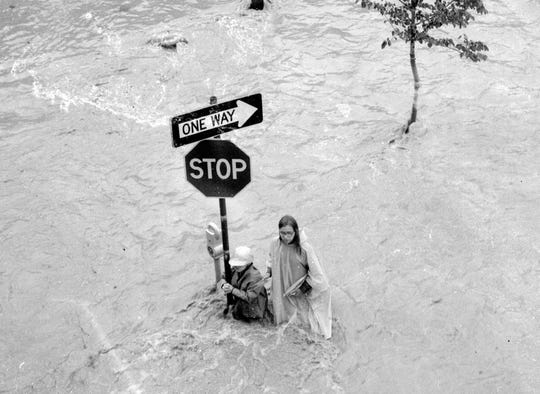 Harold G. Nixon Jr. and Patricia Nixon cling to a pole at First Street and Railroad Avenue in Elmira during the June 1972 Agnes flood.