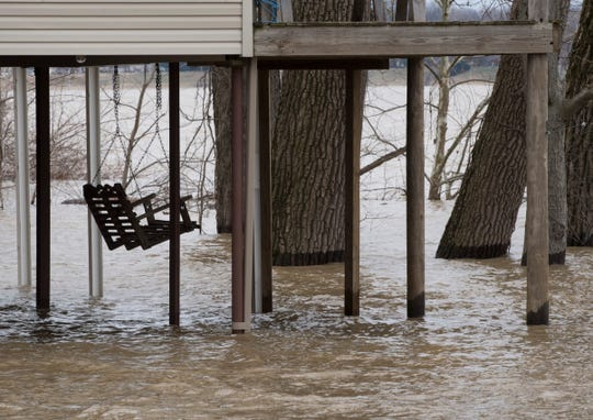 A swing is tied up high as water engulfs a river camp off Old Henderson Road Monday, Jan. 28, 2019.