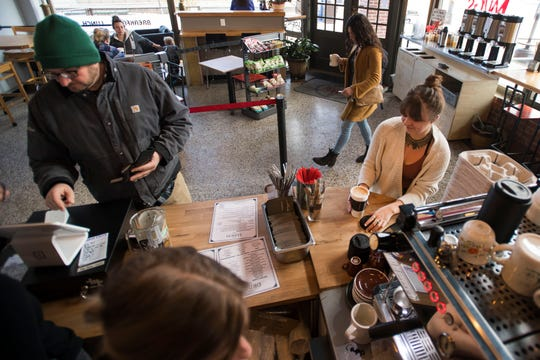 Local Kianna Lackman, right, grabs her order of a coconut milk latte on Monday, Jan. 28, 2019, at Mugs Coffee Lounge at the corner of South College Avenue and West Olive Street in Fort Collins, Colo. Mugs reopened after being closed 18 days for renovation.