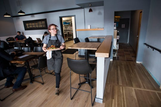 Barista and cook Shaina Crump delivers a customer's BLT sandwich on Monday, Jan. 28, 2019, at Mugs Coffee Lounge at the corner of South College Avenue and West Olive Street in Fort Collins, Colo.