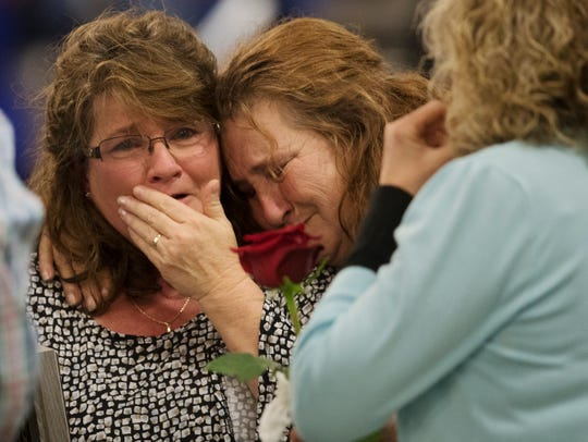 Tina Warner, left, weeps at a vigil on Sunday, Jan. 27, 2019, at the News-Sun Center in Sebring, Florida, for her daughter, Jessica Montague, and four other people killed in a shooting at a SunTrust Bank on Jan. 23 in Sebring. Hundreds of Sebring community members attended the service.