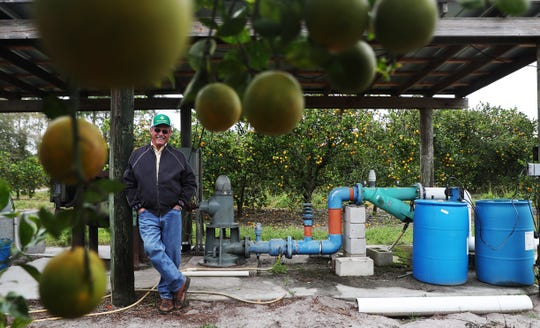 Citrus farmer Wayne Simmons stands for a portrait next to one of the water pumps that irrigates one of his orange groves near LaBelle. As a citrus grower he says supports some of Gov. Ron DeSantis's environmental policies.