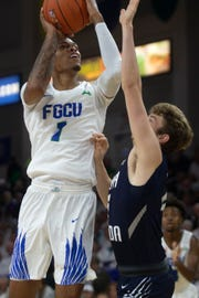 Florida Gulf Coast University's Troy Baxter Jr. takes a shot over University of North Florida's Ryan Burkhardt, Saturday, Jan. 27, 2019, at Alico Arena in Fort Myers.