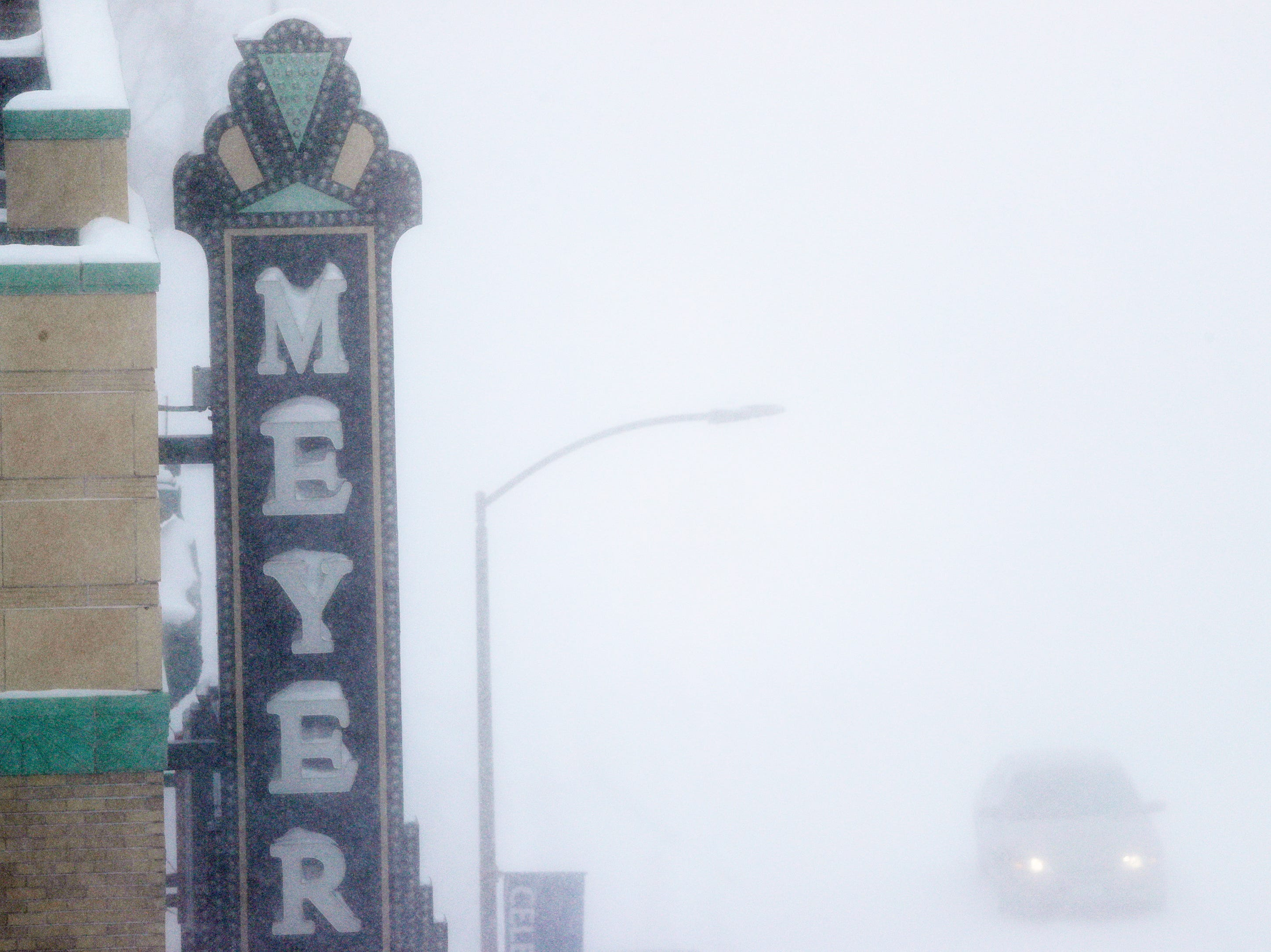 The Meyer theater sign collects snow during a snowstorm on Monday, Jan. 28, 2019 in Green Bay, Wis.