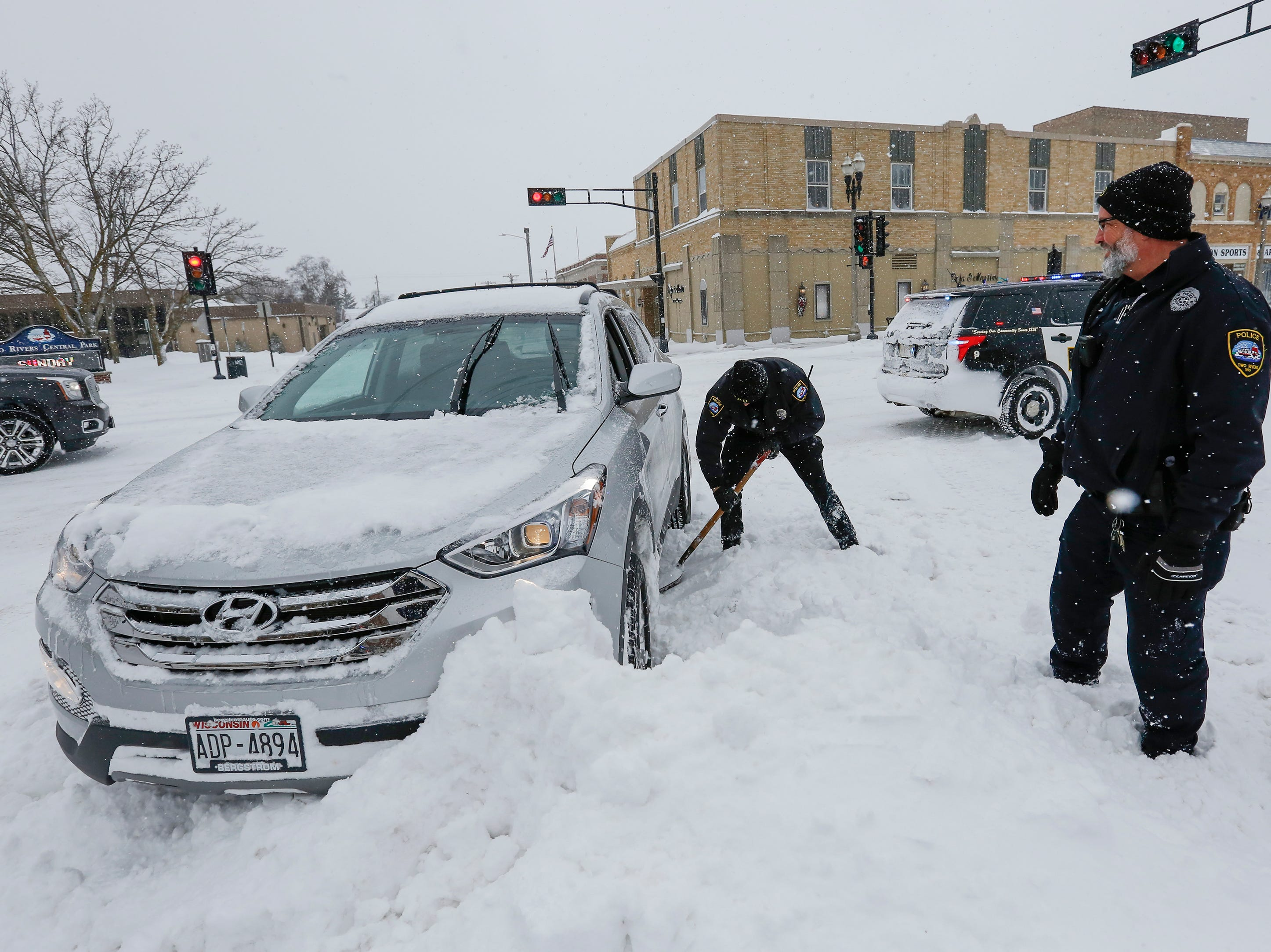 Officers Bobby Strandt, left, and Tim Culligan, of the Two Rivers Police Department, help dig out Kevin Holschbach's car after he got stuck in a snowbank off Main Street on Monday, Jan. 28, 2019, in Two Rivers, Wis.