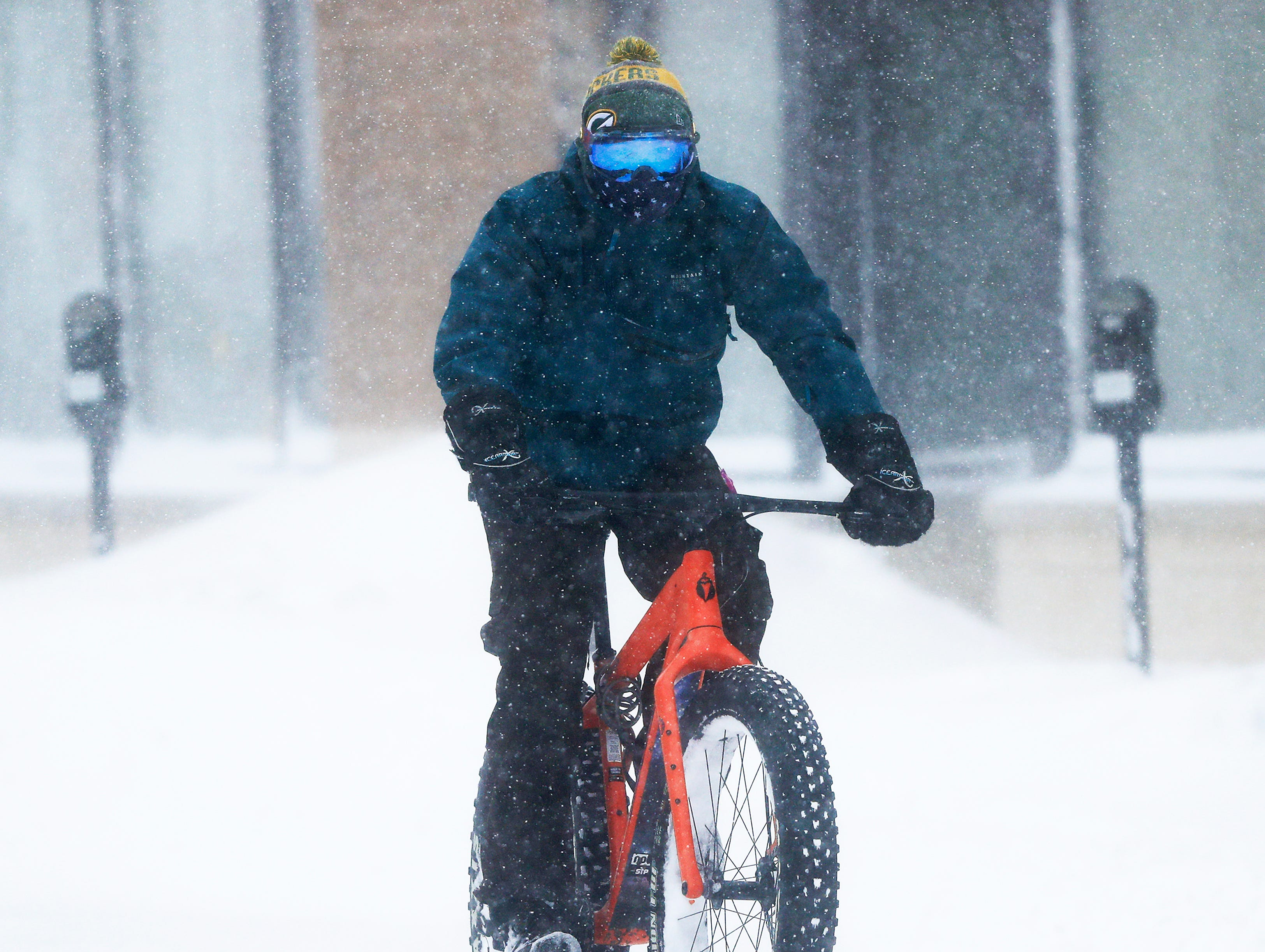 A cyclists rides downtown during a snowstorm on Monday, Jan. 28, 2019 in Green Bay, Wis.