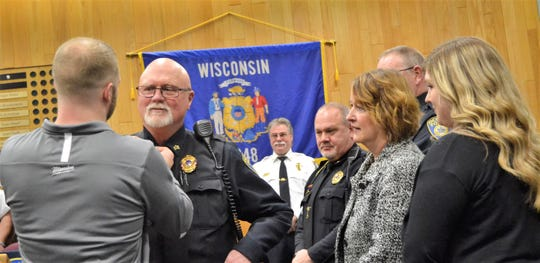 Oconto Police Officer Glenn Sowle receives his sergeant's bars from his son Drew, of Milwaukee as his wife Bonnie and daughter Lauren, of Oconto, look on.