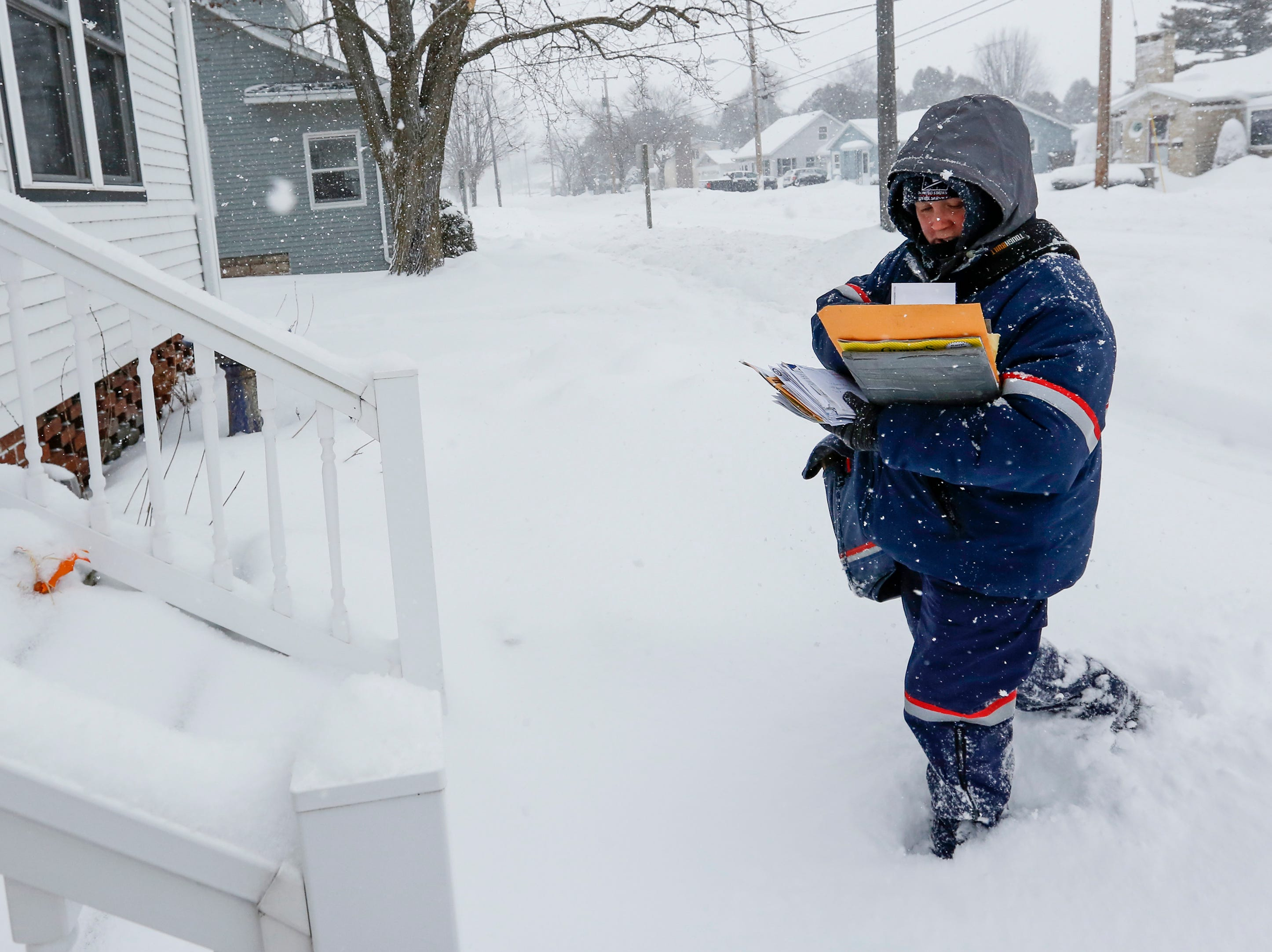 Heidi French, of the Two Rivers Post Office, delivers mail on her route during a snowstorm Monday, Jan. 28, 2019, in Two Rivers, Wis.