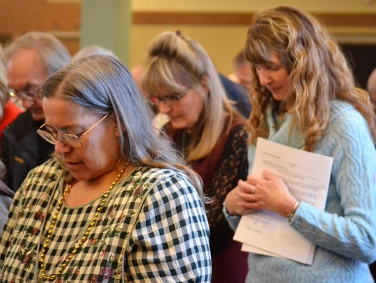 Praying at the dedication of the new Holy Trinity Catholic Church in Oconto on Sunday, Jan. 27, is Tammy Behnke, front, with Patty Gabrielson and Nancy Copeland behind her.