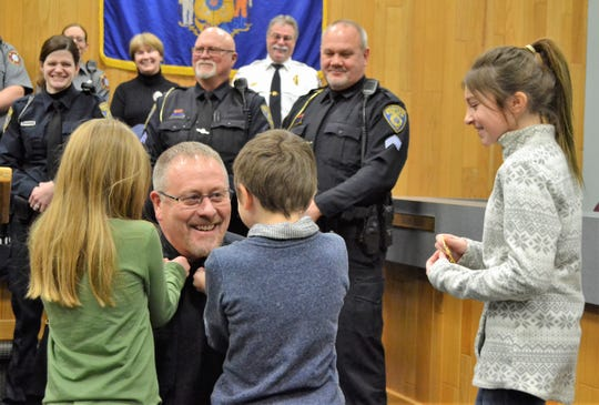 Randy Van Hulle smiles as his grandchildren, Kora Termaat, 8, and Ryder Van Hulle, 8, pin the captains bars to his collar at a ceremony Friday in the council chambers at Oconto City Hall. At right, waiting to pin on her grandfather's badge is Vayda Van Hulle, 11. Behind Van Hulle is the other three officer who pinned, Nicole Crocker, Glenn Sowle and Jeff Ruechel.