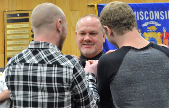 Oconto Police Officer Jeff Ruechel is pinned with his captain's bars by his sons Kyle, of Montana, and Chris, of Oconto. Granddaughter Sawyer also helped.