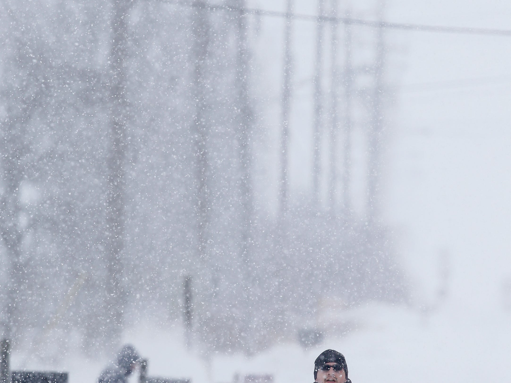 Johnny Torres, of Manitowoc, walks down Mirro Drive in a snowstorm Monday, Jan. 28, 2019, in Manitowoc, Wis.
