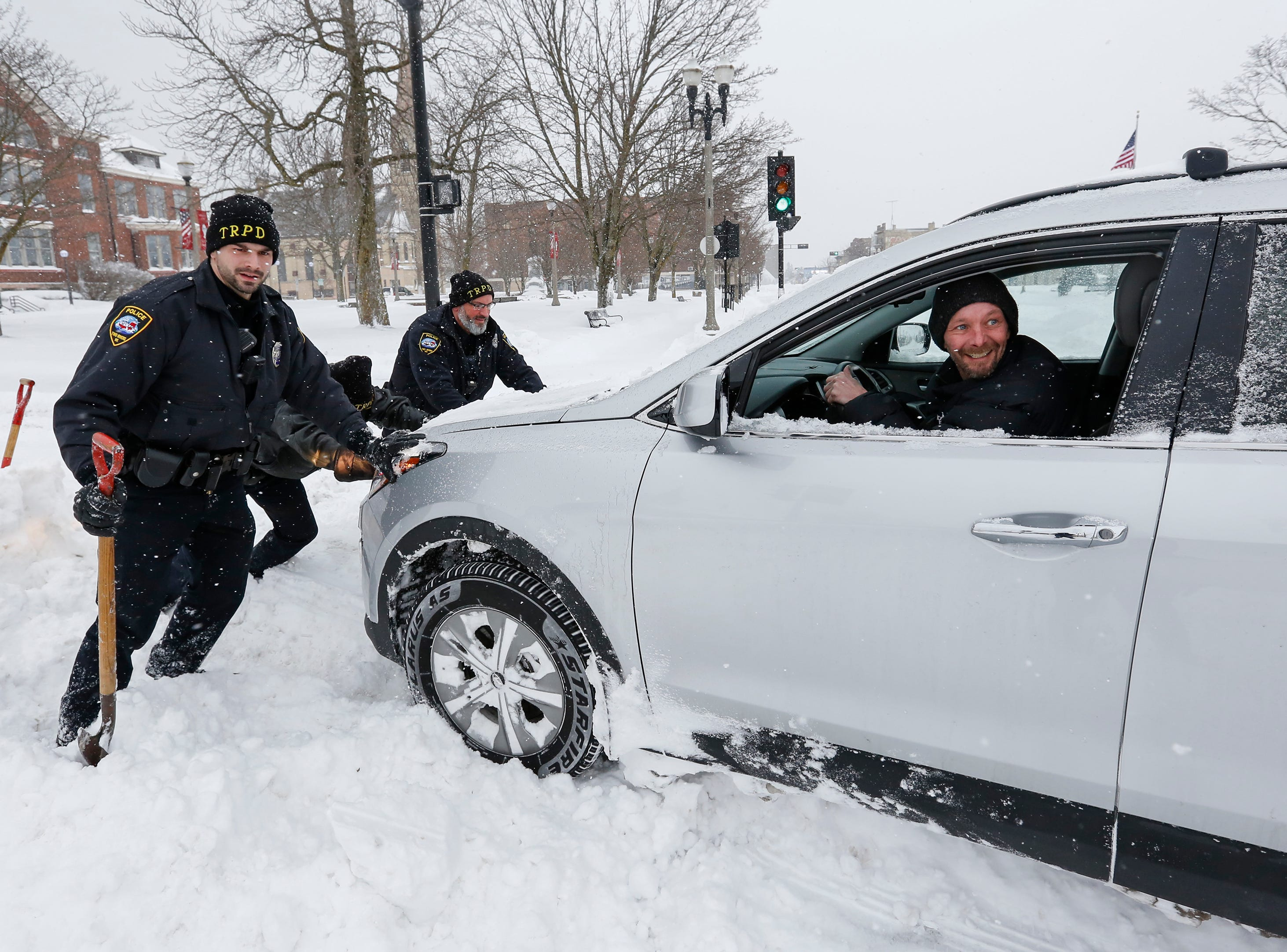 From left, Officers Bobby Strandt, Jeremy Stodola and Tim Culligan, of the Two Rivers Police Department, help push out Kevin Holschbach's car after he got stuck in a snowbank off Main Street on Monday, Jan. 28, 2019, in Two Rivers, Wis.