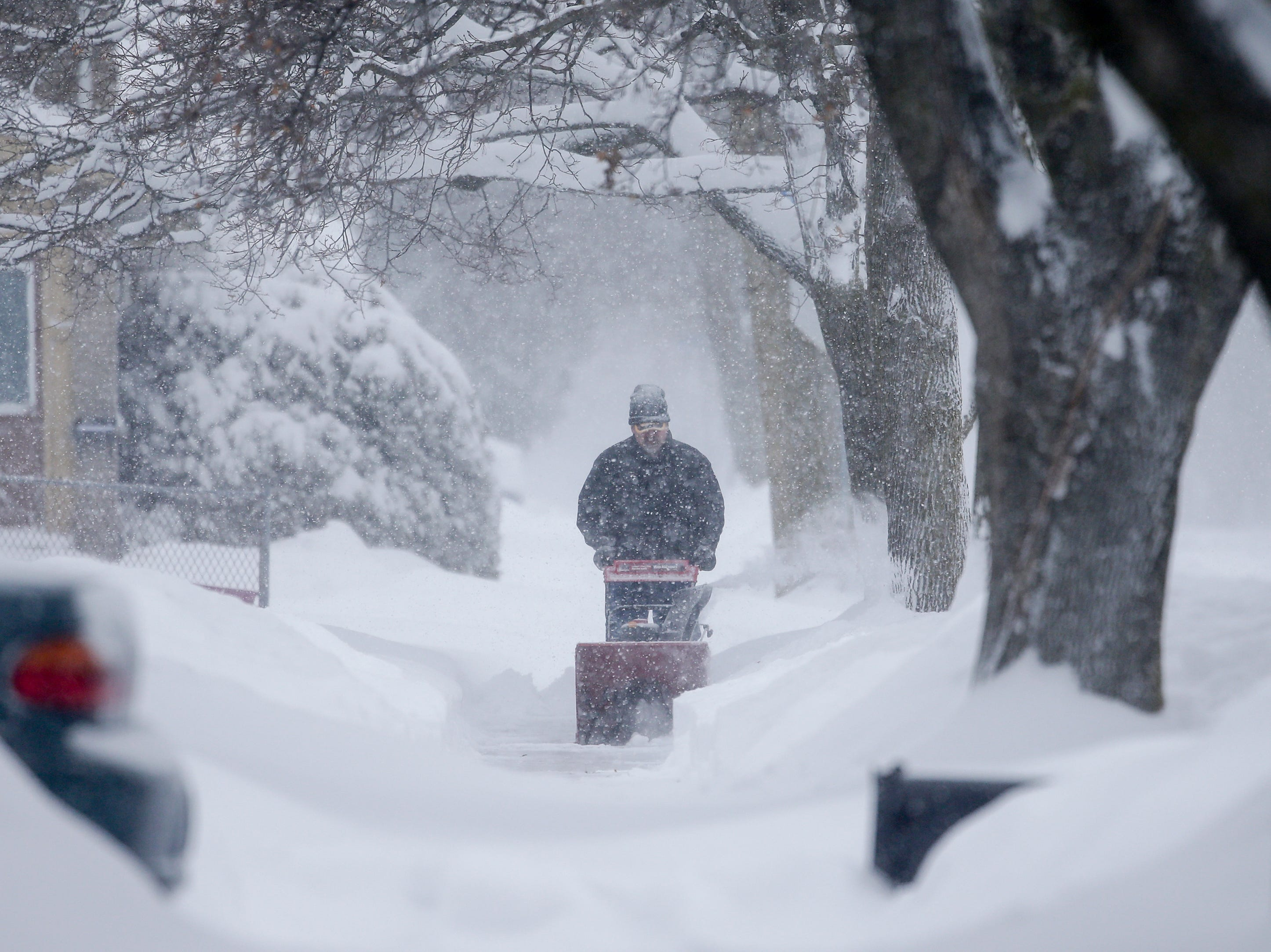 A Manitowoc resident snow blows the sidewalk as a snowstorm moves across the state Monday, Jan. 28, 2019, in Manitowoc, Wis.