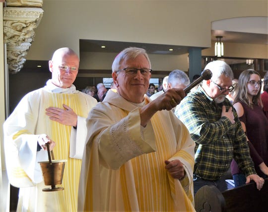 The Most Rev. David Ricken, bishop of the Green Bay Diocese, sprinkles holy water around Holy Trinity Catholic Church in Oconto during the dedication of the newly-constructed church on Sunday. Assisting at left is the Rev. Mr. William Evans, a deacon.