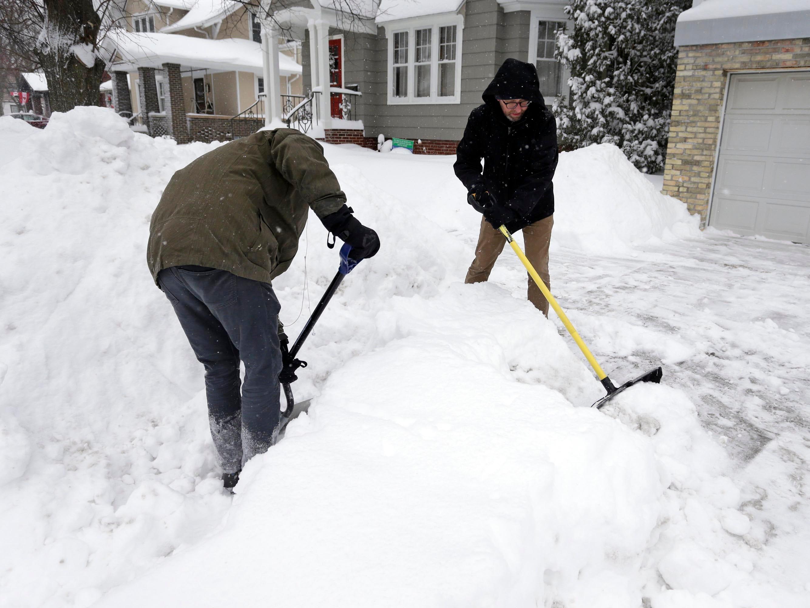 Elijah Watson, left, and David Hein, both of Sheboygan, Wis., shovel the end of the driveway by Hein's home Monday, Jan. 28, 2019, in Sheboygan, Wis.