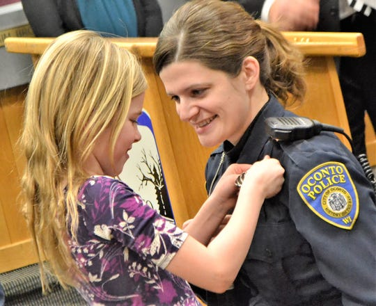 Oconto Police Officer Nicole Crocker smiles as her daughter Adeline, 7, carefully attaches her mom's new detective badge at a pinning ceremony Friday at Oconto City Hall.