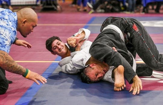 In this file photo from the 2019 Copa De Marianas Brazilian Jiujitsu Tournament, Tyler Klien in white forces his opponent Larry Vidal into submission during their adult 146-160 pound division. The registered competitors for this year's competition already exceed last year's total numbers by 100.