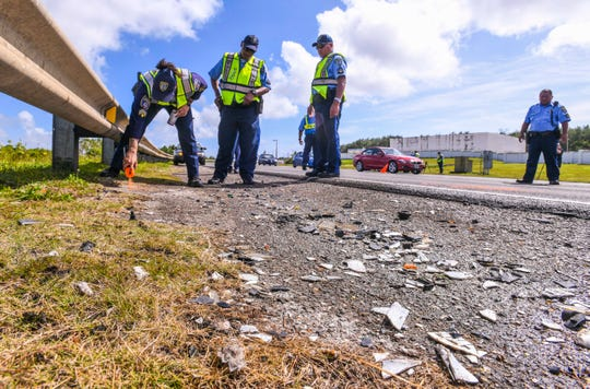 In this Jan. 9, 2019, file photo, Guam Police Department officer Morgan Reyes marks key points of interest as she and other Highway Patrol Division officers conduct a traffic accident investigation along Route 10A.