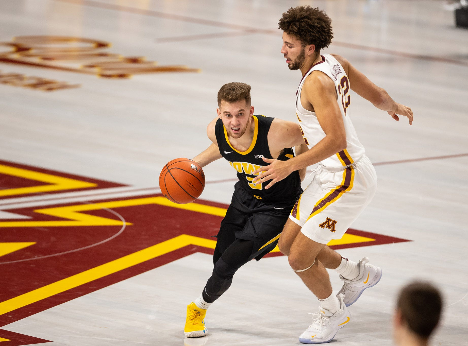Iowa Hawkeyes guard Jordan Bohannon (3) dribbles the ball as Minnesota Gophers guard Gabe Kalscheur (22) defends during the second half at Williams Arena. Mandatory Credit: Harrison Barden-USA TODAY Sports