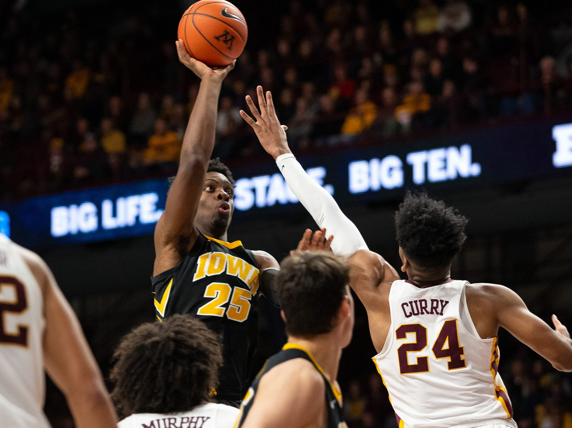 Iowa Hawkeyes forward Tyler Cook (25) shoots the ball over Minnesota Gophers forward Eric Curry (24) during the second half at Williams Arena. Mandatory Credit: Harrison Barden-USA TODAY Sports