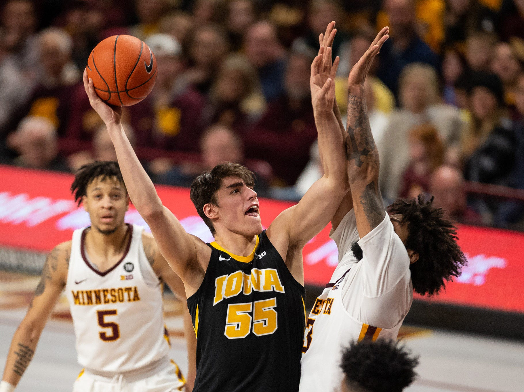 Iowa Hawkeyes forward Luka Garza (55) shoots the ball as Minnesota Gophers forward Jordan Murphy (3) defends during the second half at Williams Arena. Mandatory Credit: Harrison Barden-USA TODAY Sports