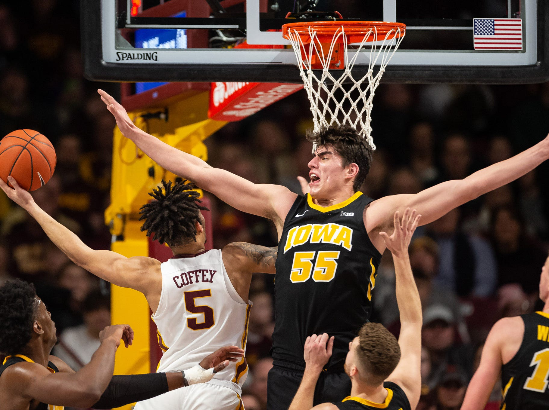 Iowa Hawkeyes forward Luka Garza (55) defends Minnesota Gophers guard Amir Coffey (5) as he drives to the basket during the second half at Williams Arena. Mandatory Credit: Harrison Barden-USA TODAY Sports