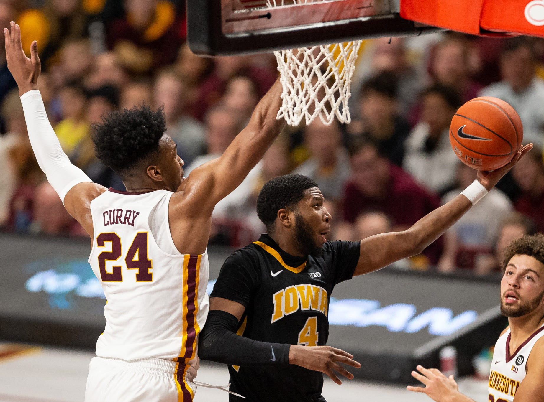 Iowa Hawkeyes guard Isaiah Moss (4) shoots the ball as Minnesota Gophers forward Eric Curry (24) defends during the second half at Williams Arena. Mandatory Credit: Harrison Barden-USA TODAY Sports