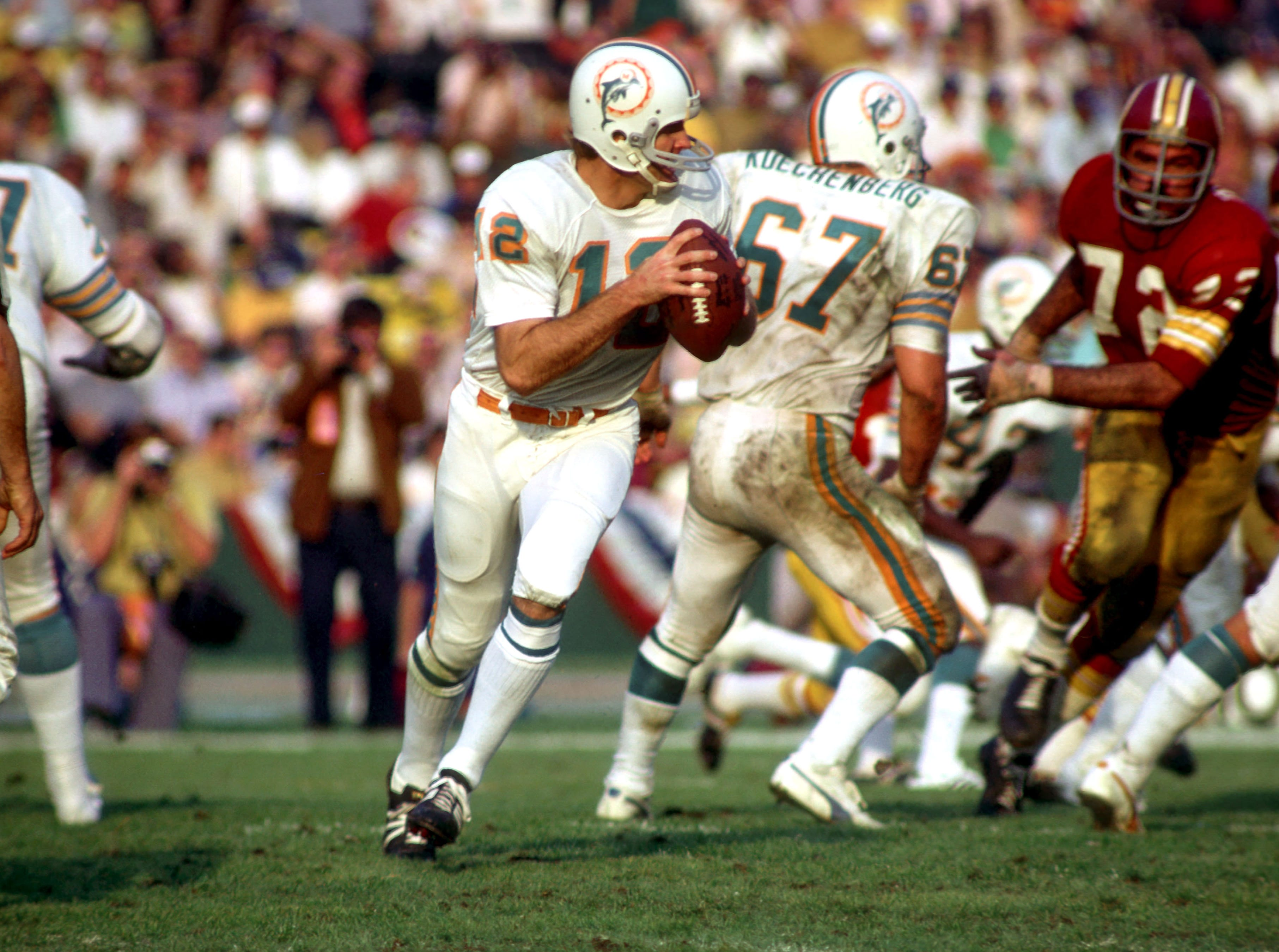 Green Bay's dominance didn't last forever, and after the merger three teams became powerhouses in the 70s. The Miami Dolphins became the first and only team to ever have a perfect season (17-0). In Super Bowl VII, they defeated the Washington Redskins (14-7) and would win the championship again the following year. (pictured: Jan 14, 1973; Los Angeles, CA, USA; Miami Dolphins quarterback #12 Bob Griese in action against the Washington Redskins in Super Bowl VII at Memorial Coliseum.)