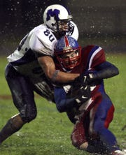 Muncie Central's Ryan Kerrigan (80) takes down Jay County's Michael Jobe.