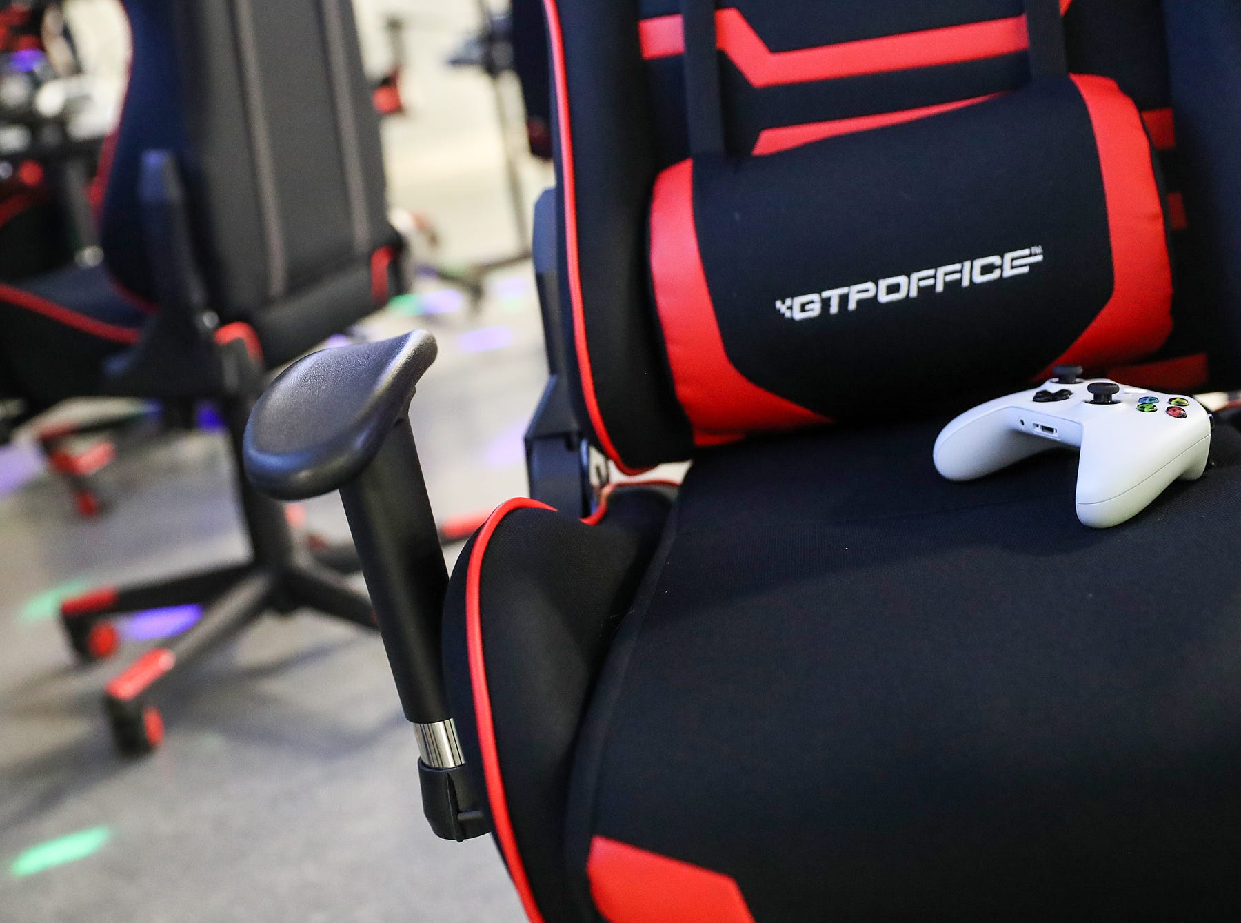A gaming chair and controller are seen during an Evolve Youth Sports practice at the Player One arena in Carmel, Ind., Thursday, Jan. 24, 2019. Scott Wise, original founder of Scotty's Brewhouse, has partnered with Player One Esports for his next venture, a video game sports league that has attracted around 200 kids so far.